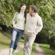 Couple on walk along woodland path — Stock Photo