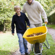 Father and son pushing wheelbarrow — Stock Photo