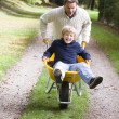 Father giving son ride in wheelbarrow — Stock Photo