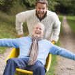 Grown up son pushing father in wheelbarrow — Stock Photo