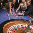 Stock Photo: Group of friends gambling in casino