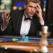 Man losing at roulette table - Stock Photo