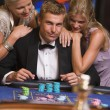 Royalty-Free Stock Photo: Man gambling in casino surrounded by attractive women