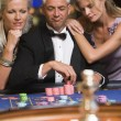 Man at roulette table with beautiful women — Stock Photo