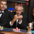 Group of male friends gambling at roulette table — Stock Photo