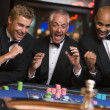 Stock Photo: Group of men celebrating win at roulette table