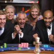 Group of friends celebrating win at roulette table — Stock Photo #4755250