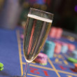 Close up of champagne glass on roulette table — Stock Photo