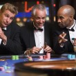 Three men gambling at roulette table - Stock Photo