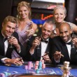 Group of friends gambling at roulette table — Stok fotoğraf