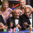 Group of friends gambling at roulette table — Stock Photo #4755285