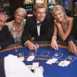 Group of friends playing blackjack in casino - Stock Photo