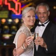 Mature couple celebrating in casino - Stock Photo