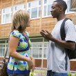 Male and female college students talking on campus — Stock Photo