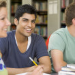 Stock Photo: College students studying together in a library