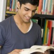 Male college student reading in a library — Stock Photo