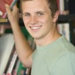 Male college student reaching for a library book — Stock Photo