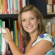 Female college student reaching for a library book - Stockfoto