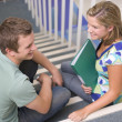Male and female college students sitting on stairs — Stockfoto