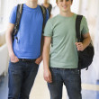 Foto Stock: Male college students standing in university corridor