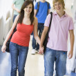 Young couple walking down university corridor — Stock Photo #4755490