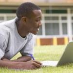 collegestudent med laptop på campus gräsmatta — Stockfoto