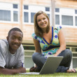 Photo: Two college students using laptop on campus lawn,