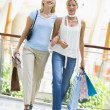 Friends shopping in mall - Stock Photo