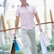 Man shopping in mall - Stock Photo