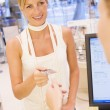 Woman paying in store - Stock Photo