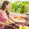Woman shopping in produce department — Stockfoto