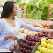 Stock Photo: Young womshopping in produce section
