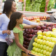 Mother and daughter in produce section — Stock Photo #4757674