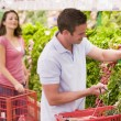 Couple flirting in supermarket aisle - Stock Photo