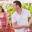 Couple flirting in supermarket — Stock fotografie