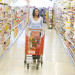 Royalty-Free Stock Photo: Woman pushing trolley along supermarket aisle