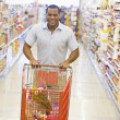 Man pushing trolley along supermarket aisle — Stockfoto