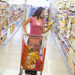 Woman shopping in supermarket aisle — Foto de Stock