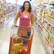 Woman pushing trolley along supermarket aisle - Stock Photo