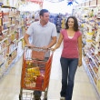 Couple shopping in supermarket aisle — Stock Photo