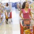 Two women shopping in supermarket - Stock Photo