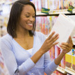Woman checking food labelling in supermarket — Stock Photo #4757736