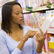 Female shopper checking food labelling — Stock Photo