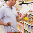 Man checking food labelling in supermarket - Stock Photo