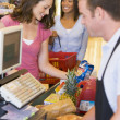 Woman paying for groceries - Stock Photo
