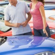Couple looking at new cars — Stock Photo