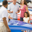 Family discussing new car with salesman — Stock Photo