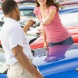 Woman picking up keys to new car — Stock Photo
