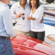 Couple picking up new car from salesman - Stock Photo