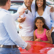 Young family picking up new car - Stock Photo
